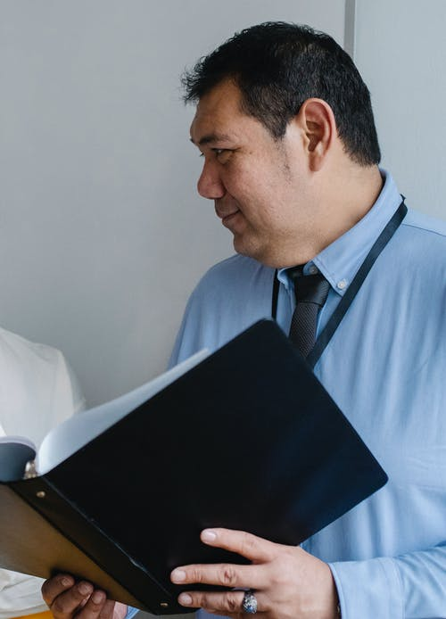 Smart mature male manager holding documents folder and looking away