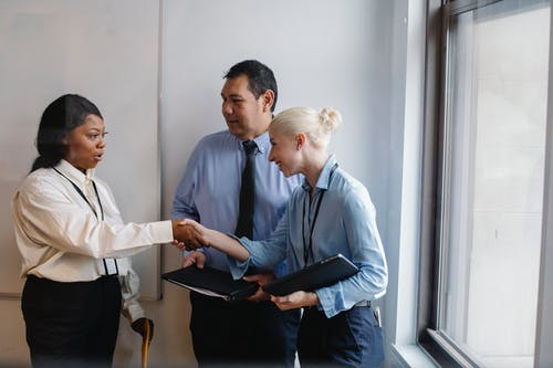 Group of diverse business partners shaking hands in office