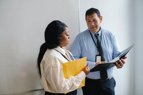 Positive multiethnic coworkers examining documents in office hallway