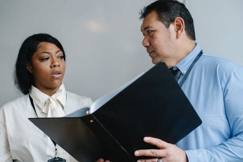 Serious middle aged male manager in shirt showing folder with documents to attentive female African American colleague during work in modern office