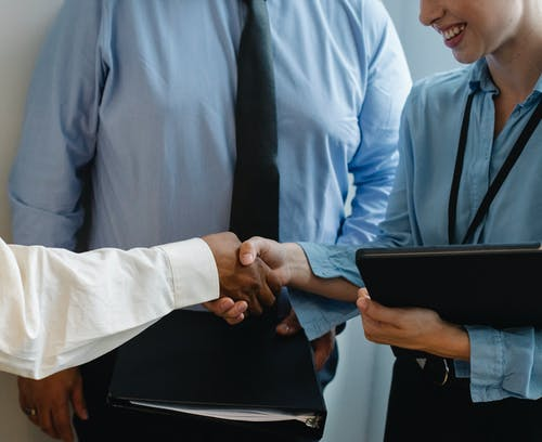 Anonymous colleagues shaking hands and smiling after meeting