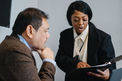 Serious African American female manager in formal outfit reading contract details to concentrated middle aged male executive in office