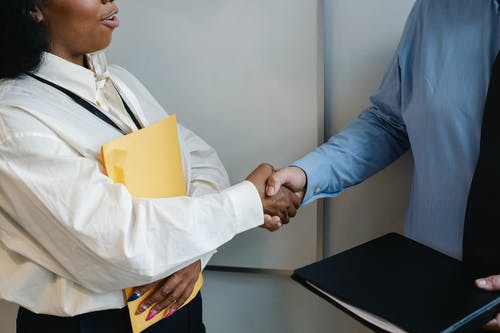 Diverse coworkers shaking hands after meeting