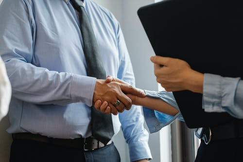 Crop anonymous man in formal shirt and tie shaking hand of woman with black folder while meeting in office