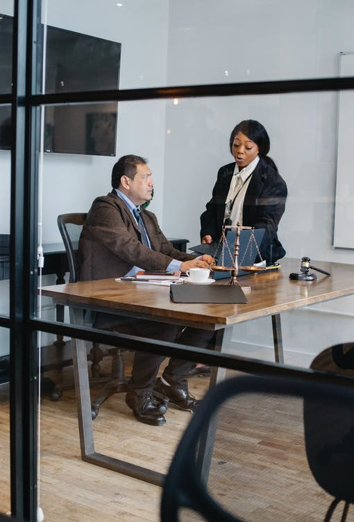View through glass of serious black woman in formal suit explaining opinion to interested mature colleague in light office with judge gavel and scales on table