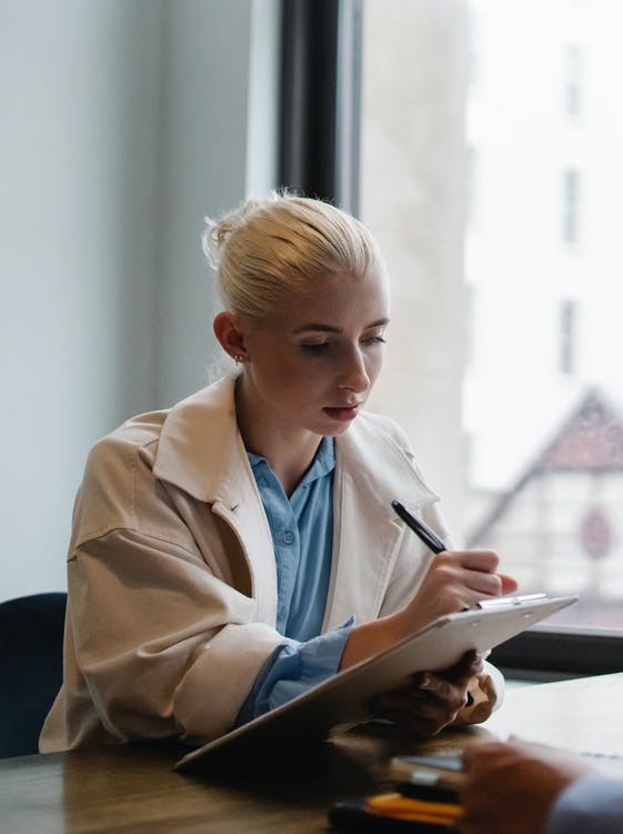 Young concentrated woman making notes on clipboard in light workplace