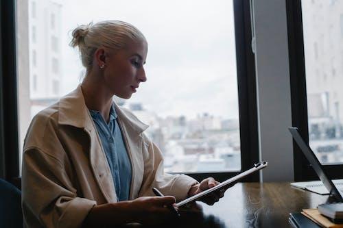 Mujer Concentrada Leyendo Informe En El Portapapeles En El Espacio De Trabajo