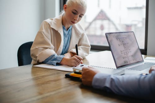 Serious young female manager in formal outfit sitting and signing documents while business partner working on laptop