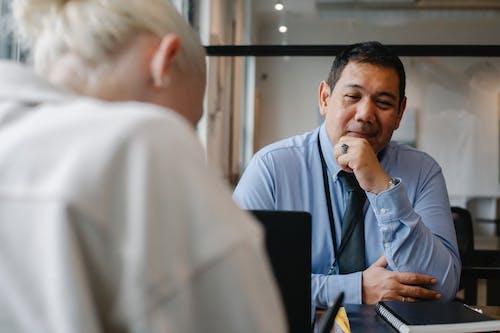 Responsabile Etnico Positivo Guardando Cliente Seduto In Ufficio