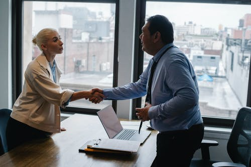 Young woman shaking hands with boss after business presentation