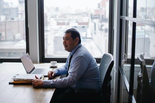 オフィスセンターでラップトップに取り組んでいるポジティブな民族男性起業家