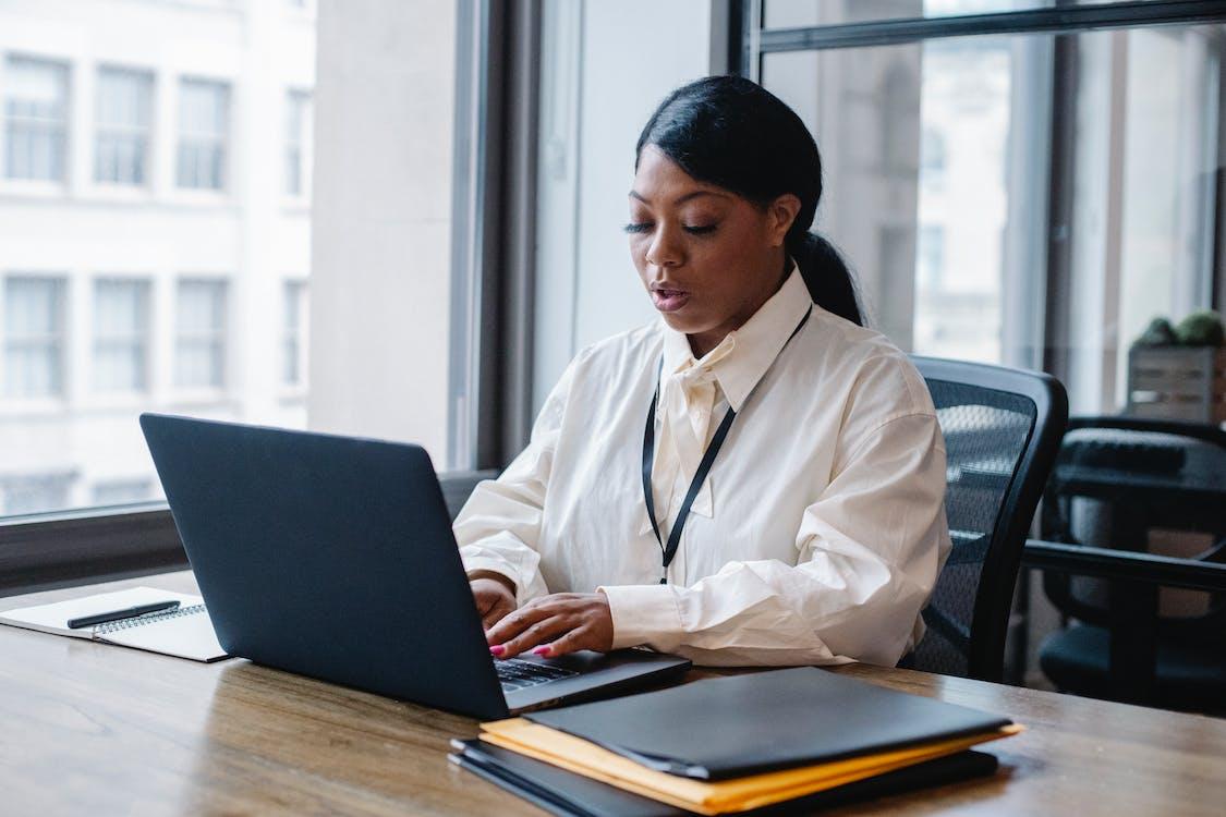 Serious black businesswoman typing text on laptop