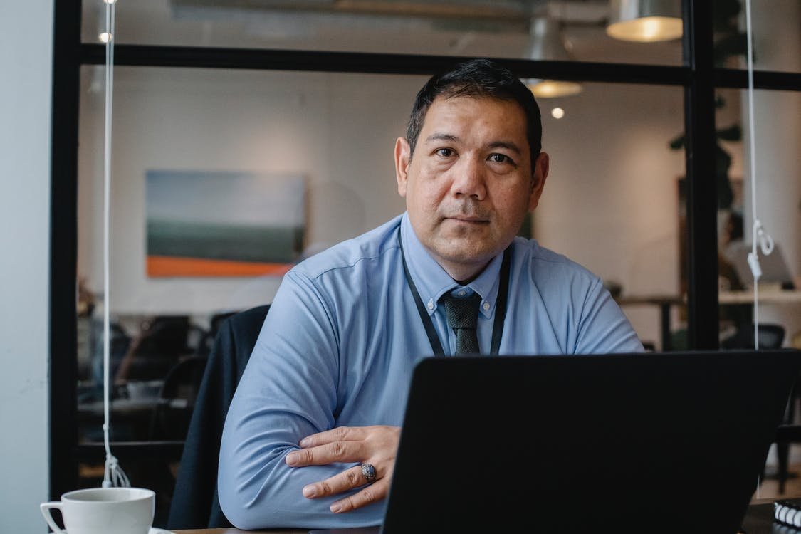 Confident ethnic male entrepreneur using laptop during business work in modern workspace and looking at camera