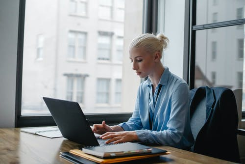 Serious woman typing on laptop in workspace