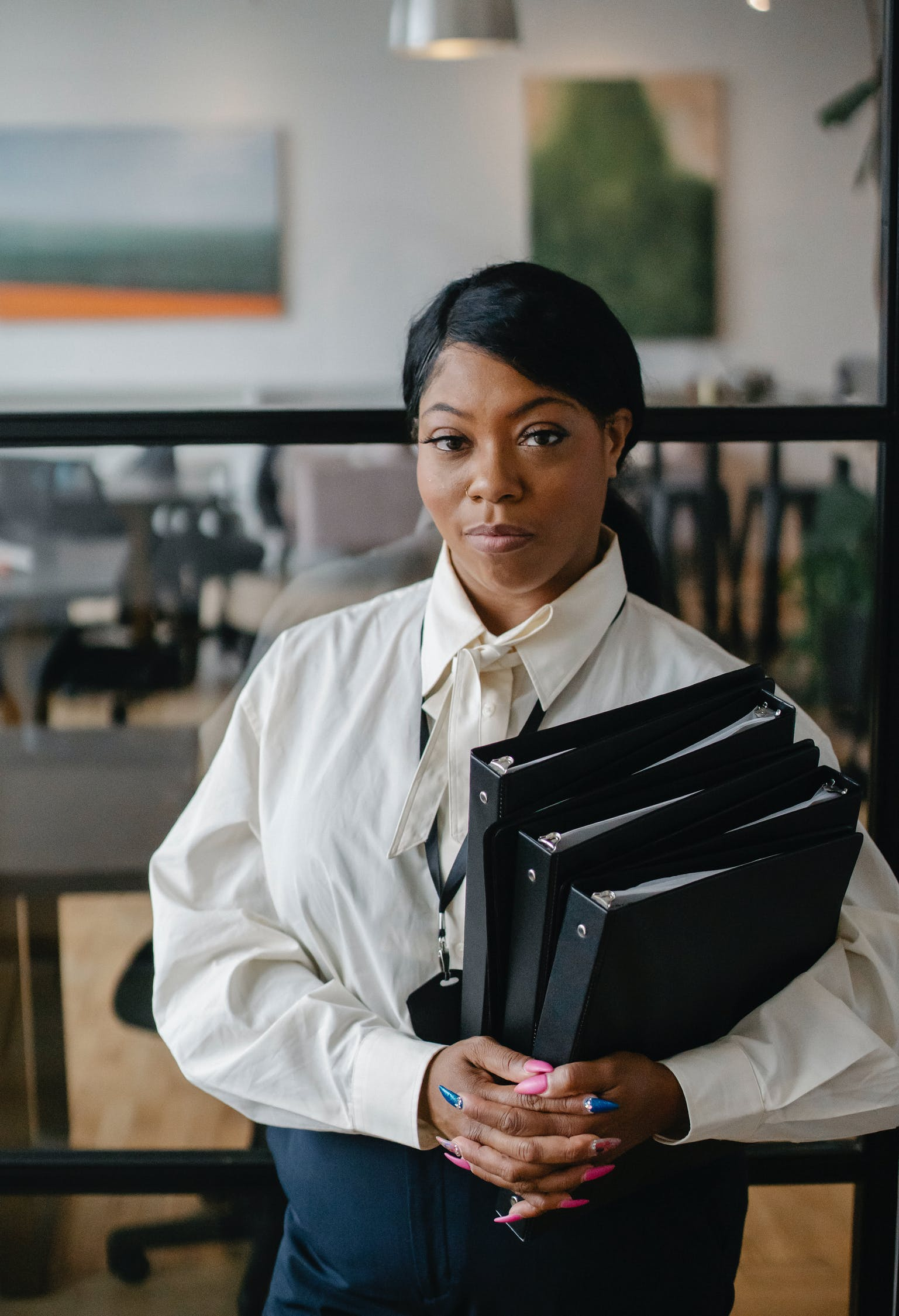 Serious black female employee with files in folders