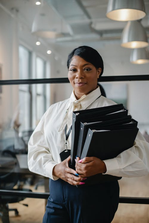 Smiling African American female employee wearing classy outfit standing with paper documents in modern workplace