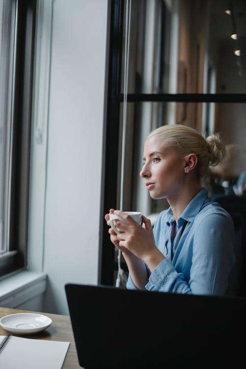 Mulher Séria Tomando Café No Escritório E Olhando Pela Janela