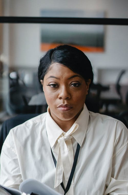 Serious black woman with papers in office
