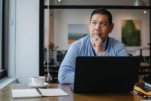 Homem De Negócios étnico Atencioso Usando Laptop Enquanto Trabalhava No Escritório