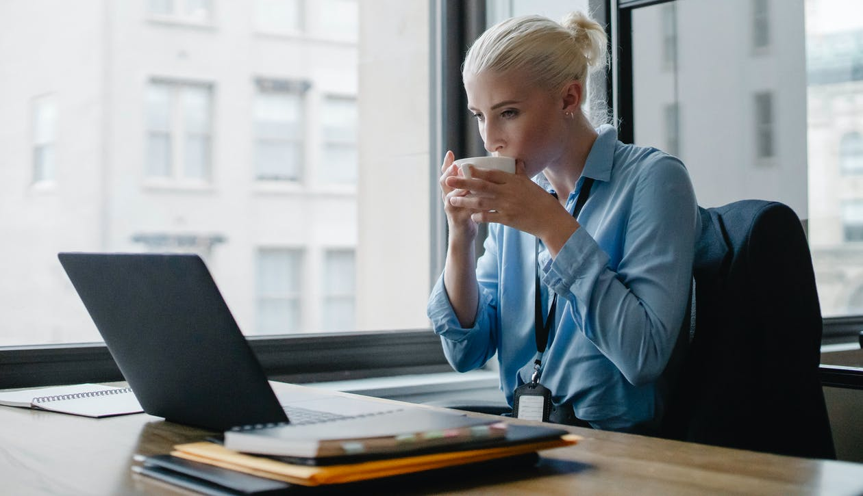 Female manager drinking coffee at workplace