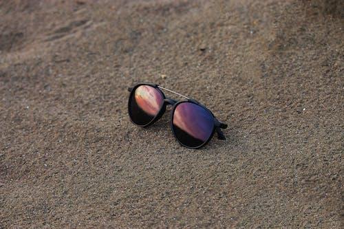Black Framed Sunglasses on Brown Sand
