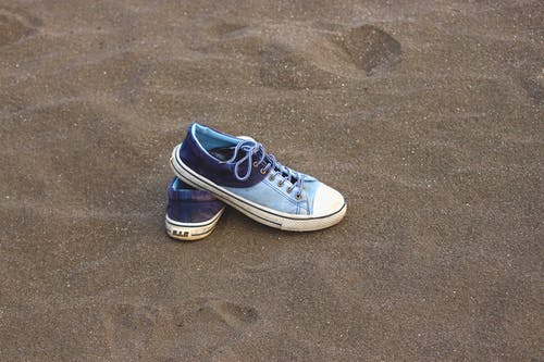 Black and White Low Top Sneakers on Brown Sand