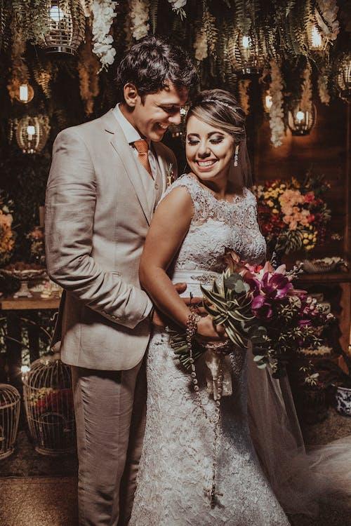 Happy smiling newlyweds hugging on wedding celebration