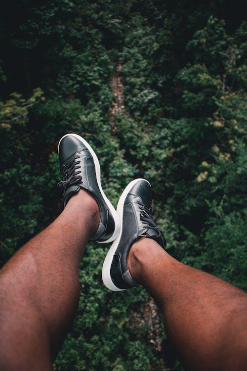 Feet of crop person wearing sneakers