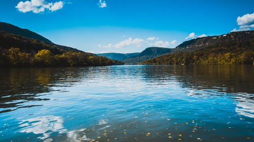 Picturesque scenery of tranquil rippling lake surrounded by verdant green hilly shores beneath cloudless blue sky on clear summer day