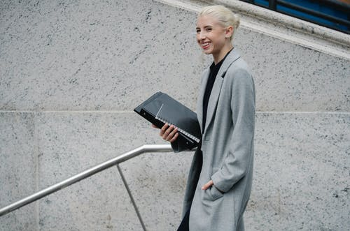 Cheerful businesswoman with folders walking on building stairs