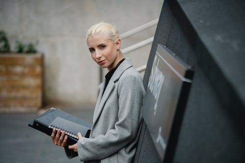 Side view attractive young businesswoman in gray coat standing with documents in folder on street