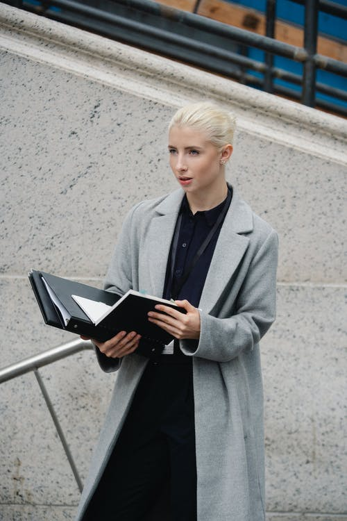 From above young concentrated businesswoman in formal clothes standing on street with opened folder and looking away in thoughts