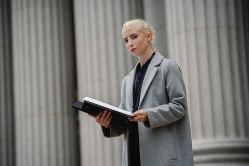 Thoughtful young businesswoman in gray coat standing with opened documents folder outside stone building pillars and looking at camera