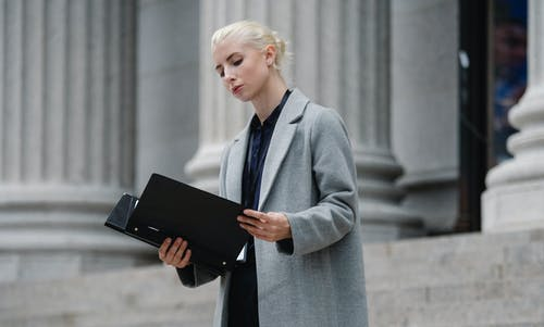 Contemplative businesswoman reading papers in folder outside building