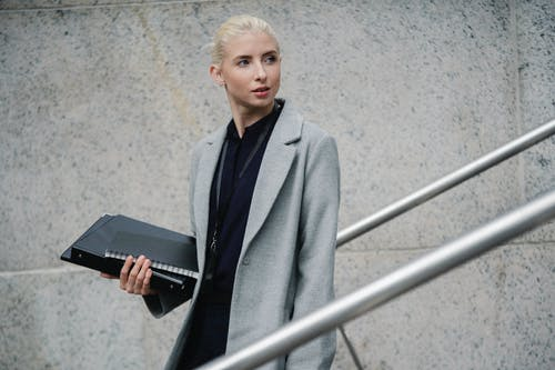 Calm young businesswoman in formal gray coat carrying folders and standing on street while looking away