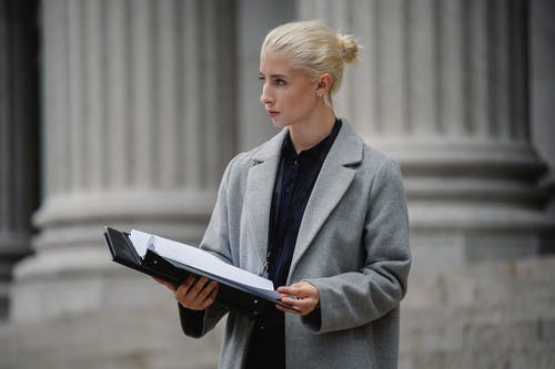 Serious young businesswoman in formal clothes standing outside stone building columns with opened folder and looking away thoughtfully
