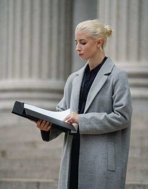 Focused young businesswoman in elegant formal clothes reading contract in folder while standing outside building pillars