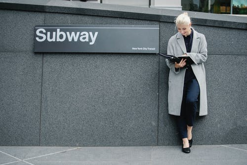 Full body smiling young businesswoman in formal clothes and coat reading documents and standing near subway station entrance