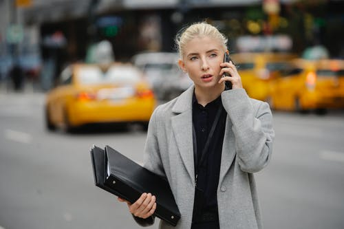 Focused young businesswoman in gray coat standing on busy street with folders and having conversation on mobile phone