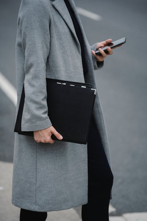 Side view crop female in elegant coat standing on street with document folder and browsing mobile phone