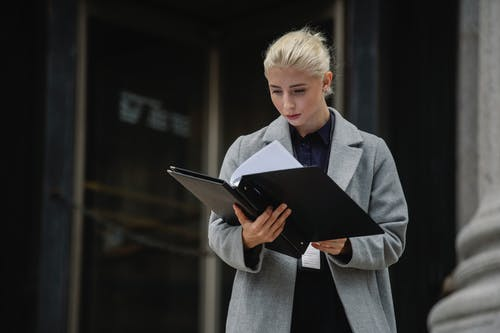 Concentrated businesswoman reading report outside office building