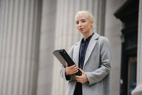 Emotionless businesswoman with paper folder standing outside modern building