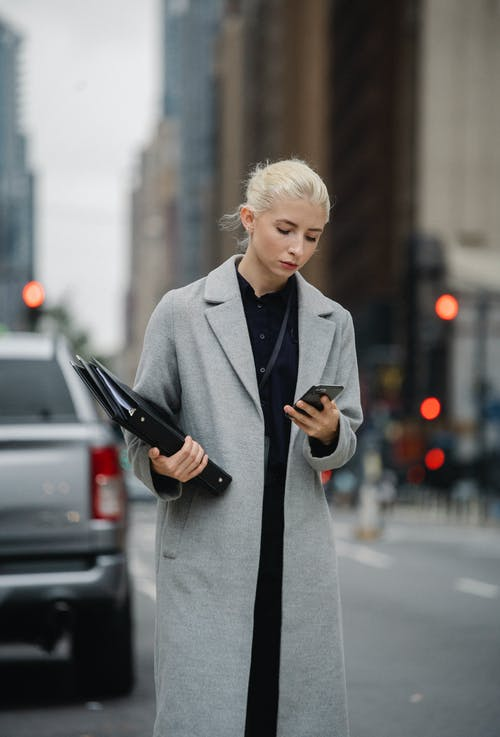 Focused young businesswoman wearing trendy coat standing on busy roadside with documents in hands and browsing modern mobile phone