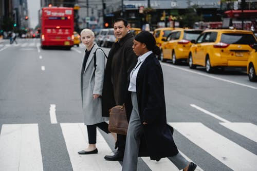 Positive multiethnic businesspeople crossing road in downtown