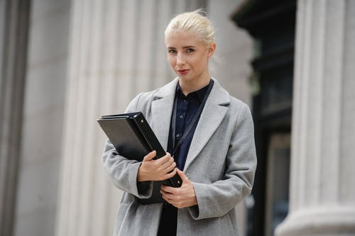 Confident businesswoman with folders standing outside stone building