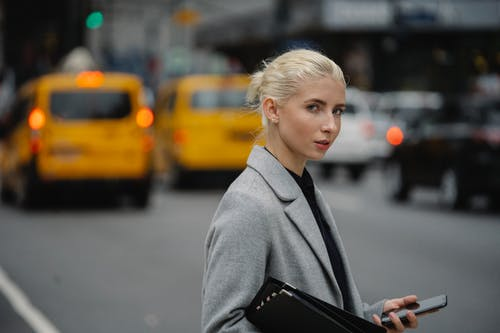 Side view focused young female in formal wear with paper folder and smartphone standing on busy street and looking at camera
