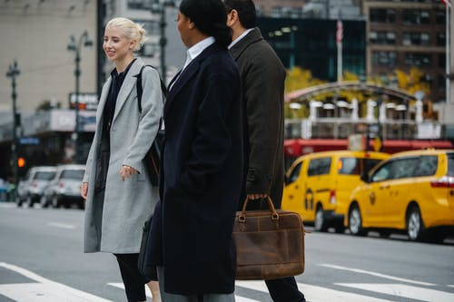 Cheerful diverse colleagues crossing road in downtown