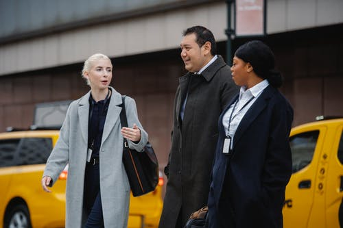 Positive multiracial coworkers in formal clothes walking together on street and discussing news on autumn day