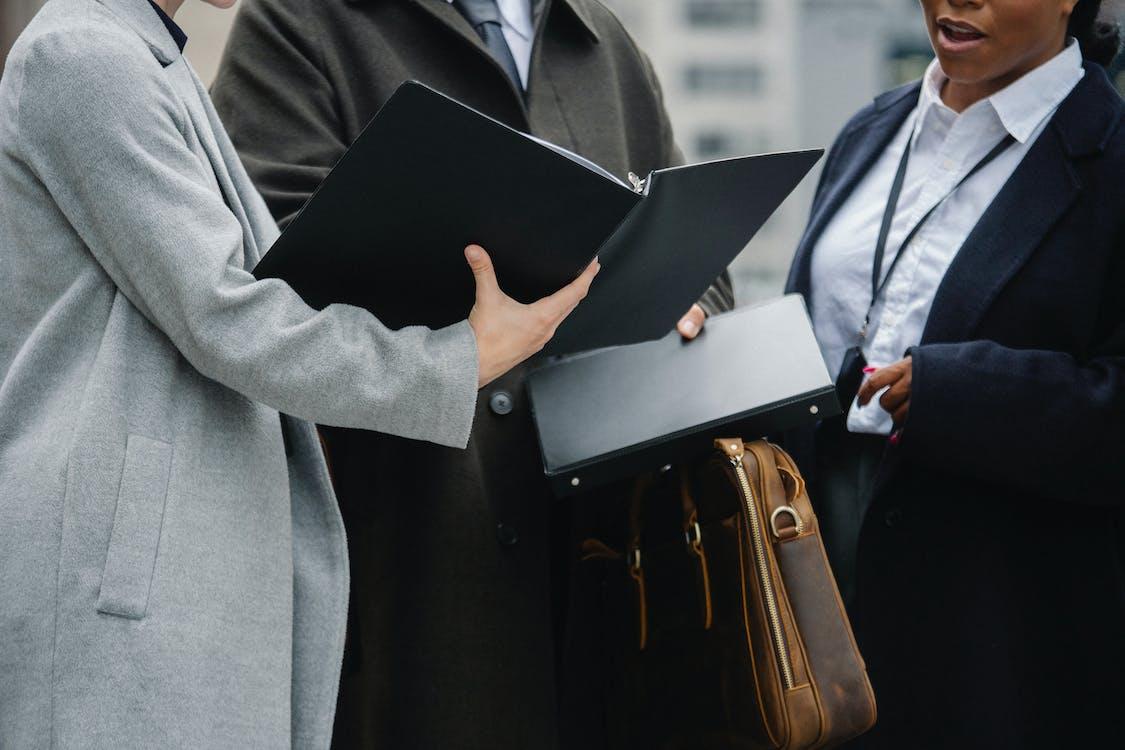 Урожай многорасовых бизнесменов, читающих документы на улице