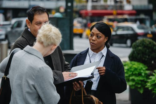 Multiethnic colleagues with documents standing on urban street